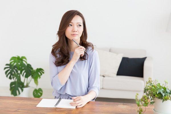 考えを紙に書く女性