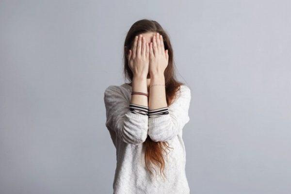 恥ずかしくて顔を隠す女性