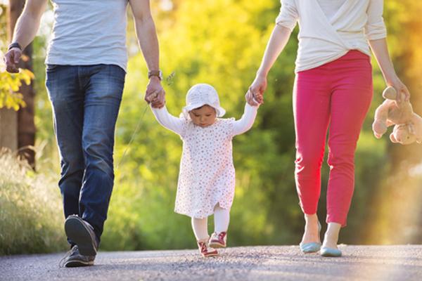 子供が両親と両手を繋いで歩く