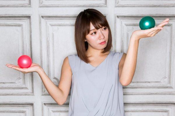 緑と赤のボールを比較する女性