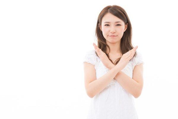 手でバツを示す女性