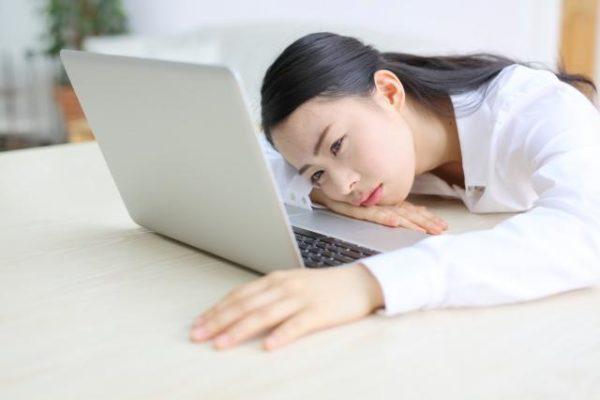 パソコンを見る疲れた女性