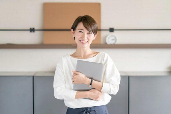 ノートパソコンを抱えて微笑む女性