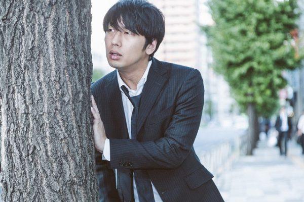 木に隠れるスーツの男性