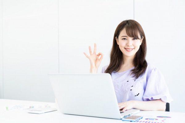 パソコンを開いてOKサインの女性