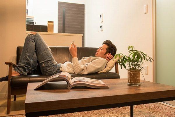 部屋のソファでくつろぐ男性