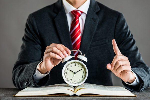 時計を持って人差し指を立てるビジネスマン