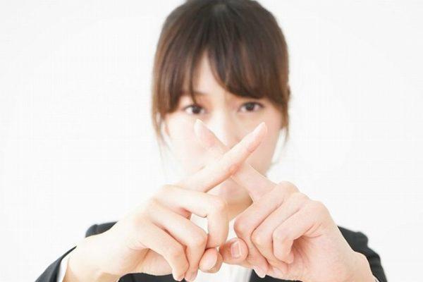 指でバツをする女性