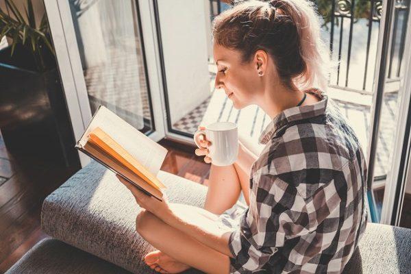 窓際でコーヒーを飲みながら本を読む女性