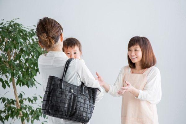 保育士に子供を預ける母親
