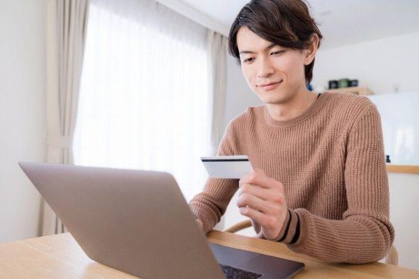 パソコンにカード情報を入力する男性