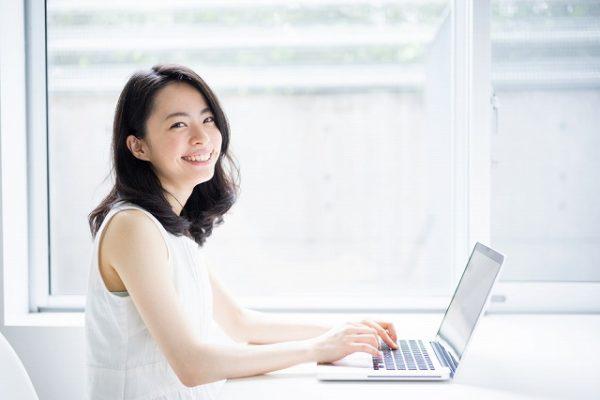 パソコンをしながらこっちを見て微笑む女性
