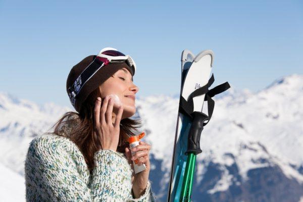スキー場で日焼け止めを塗る女性