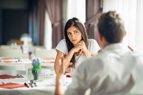話し相手の男性を疑いの目で見る女性