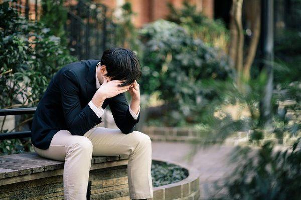 公園のベンチで凹む男性