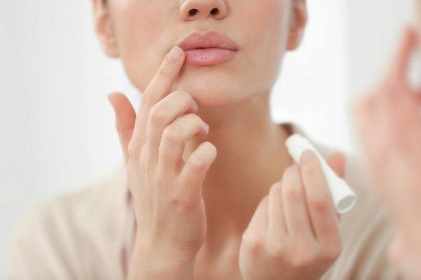 鏡を見ながら口紅を塗る女性