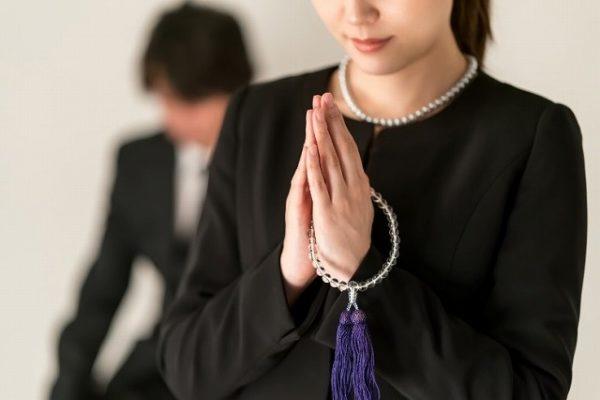 葬式で手を合わす女性