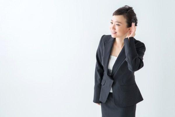 耳を傾けて話を聞くスーツの女性