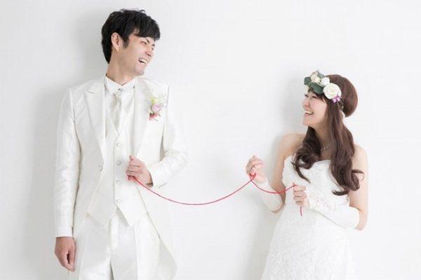 赤い糸でつながっている結婚式の新郎新婦