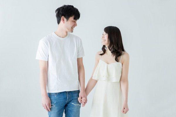 手をつないで微笑み合うカップル