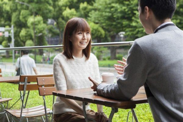 カフェのテラス席で話をする男女