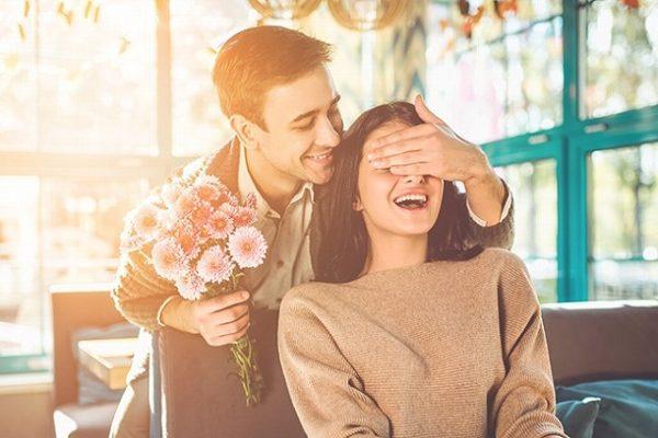後ろから目隠しをして彼女に花を渡す男性