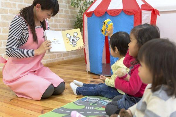 園児に絵本を読み聞かせする保育士の先生