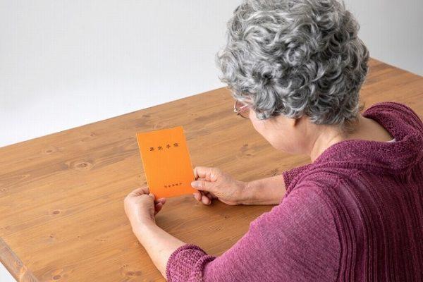 年金手帳を見るおばあさん