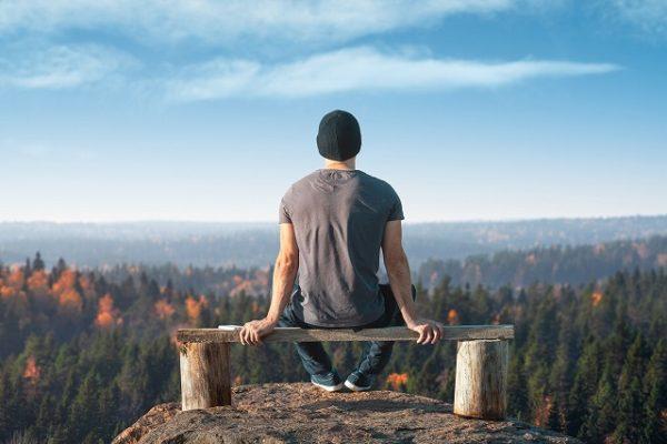 山の上のベンチに座って景色を見る男性