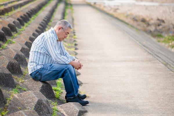 悩みを抱えて座り込んでいる年寄り男性